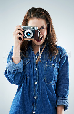 Buy stock photo Studio portrait of a young woman using a vintage camera against a grey background