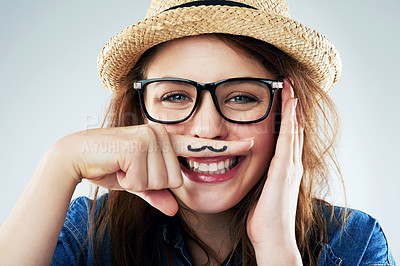 Buy stock photo Studio portrait of a young woman holding her finger under her nose with a moustache drawn on it