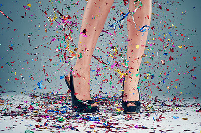 Buy stock photo Studio shot of a young woman's legs in a pair of heels with confetti falling around against a grey background