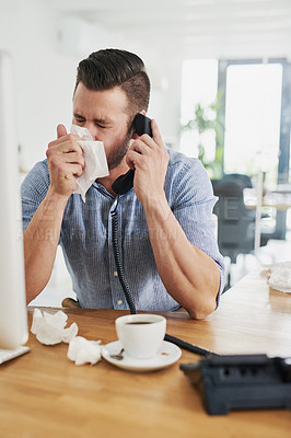 Buy stock photo Cropped shot of a young businessman blowing his nose while speaking on the phone in an office