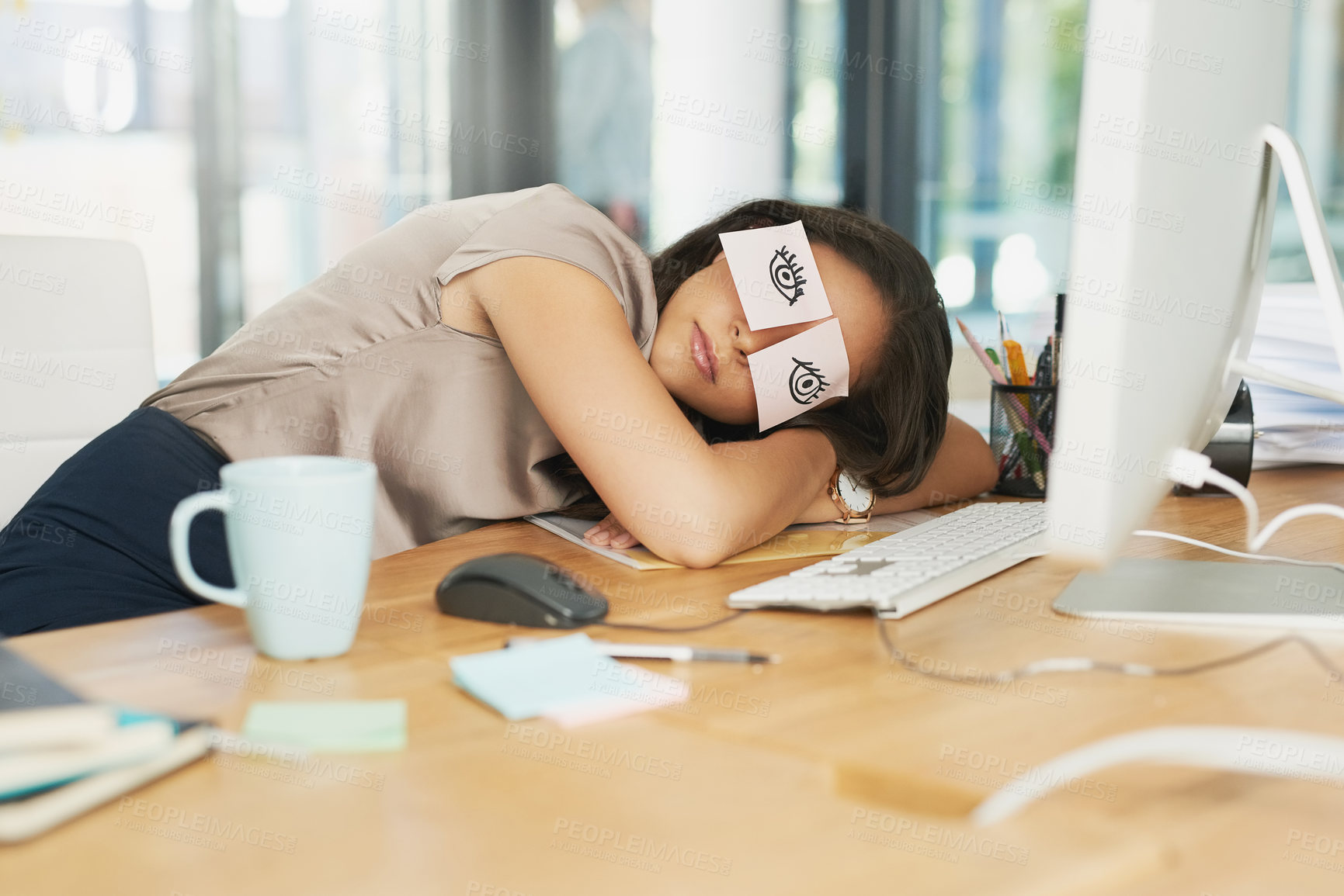Buy stock photo Shot of a tired businesswoman napping at her desk with adhesive notes on her eyes
