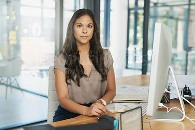 Buy stock photo Portrait of a confident young businesswoman sitting at her desk in the office