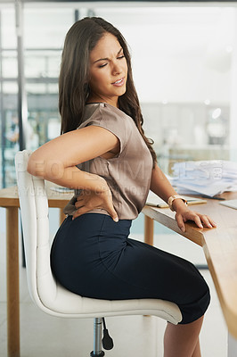 Buy stock photo Shot of a young businesswoman frowning while holding a sore spot on her back