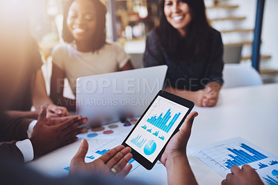 Buy stock photo Shot of a group of young businesspeople using wireless technology during a meeting in the office