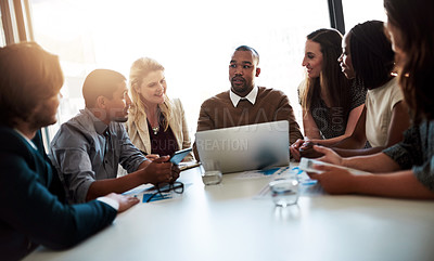 Buy stock photo Shot of a team of young businesspeople brainstorming together around a laptop in the office