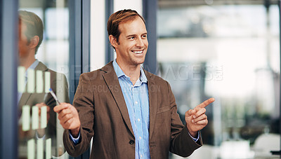 Buy stock photo Shot of a businessman presenting his ideas during a brainstorming session with adhesive notes at work