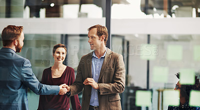 Buy stock photo Shot of colleagues shaking hands during a meeting at work