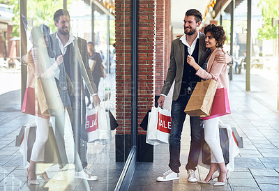 Buy stock photo Shot of a couple looking at something that on display in a shop's window