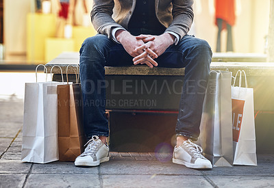 Buy stock photo Shot of a man sitting on a bench with his shopping bags on the floor