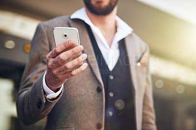 Buy stock photo Cropped shot of a young man using his cellphone while standing outside