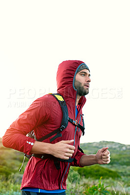 Buy stock photo Shot of a focused young man out for a run on a cool morning