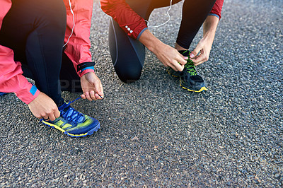 Buy stock photo Cropped shot of two friends tying up their running shoes while out for a jog