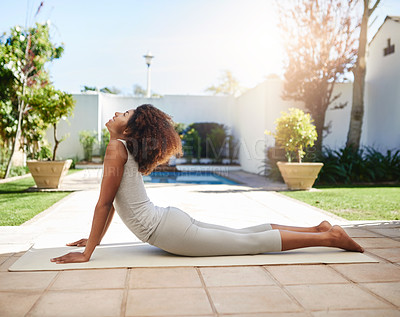 Buy stock photo Full length shot of a sporty young woman practicing yoga outdoors