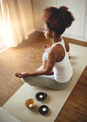 Buy stock photo High angle shot of a sporty young woman practicing yoga indoors
