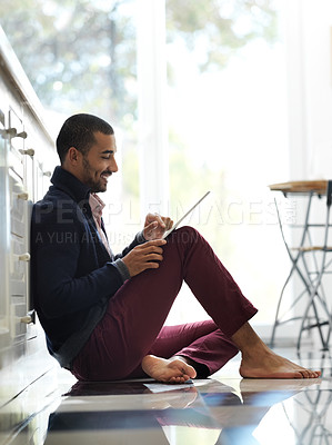 Buy stock photo Shot of a smiling young man sitting on his kitchen floor using a digital tablet