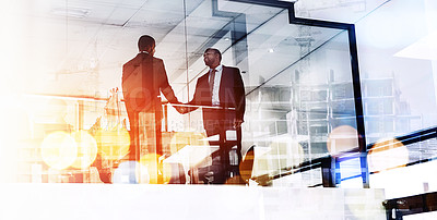 Buy stock photo Shot of two businessmen shaking hands superimposed over a cityscape
