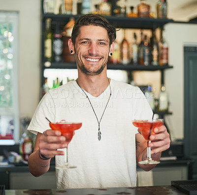 Buy stock photo Portrait of a happy young bartender holding two cocktails while standing behind the bar