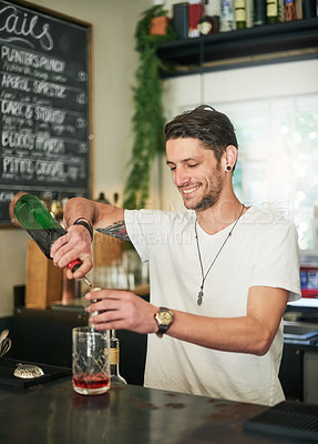 Buy stock photo Shot of a happy young bartender mixing a cocktail while standing behind the bar