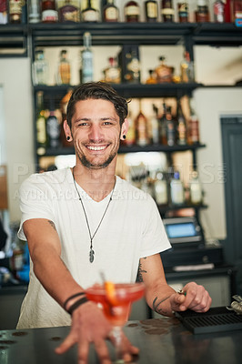Buy stock photo Portrait of a happy young bartender serving a cocktail behind the bar