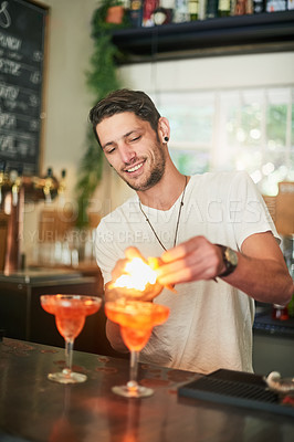 Buy stock photo Shot of a happy young bartender lighting a cocktail on fire behind the bar