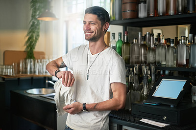 Buy stock photo Shot of a happy young waiter  polishing a glass behind the bar