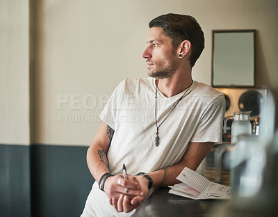Buy stock photo Shot of a serious young bartender leaning on the bar counter