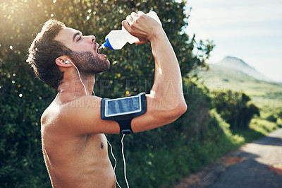 Buy stock photo Shot of a young man drinking from a water bottle while taking a break from an early morning run
