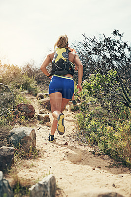 Buy stock photo Rearview shot of a young man running alone outside on a trail