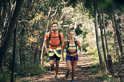 Buy stock photo Shot of two young friends running together along a trail in a forest