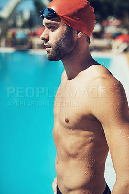 Buy stock photo Shot of an athletic young man in swimwear standing by a pool