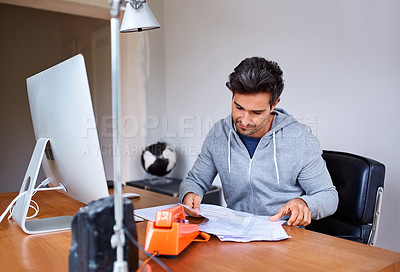 Buy stock photo Shot of a young man sitting at a desk in his home office reading documents and working on a computer