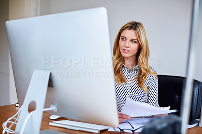 Buy stock photo Shot of a young woman sitting at a desk in her home office reading documents and working on a computer