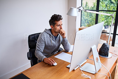 Buy stock photo Shot of a young man working on a computer while sitting at a desk in his home office
