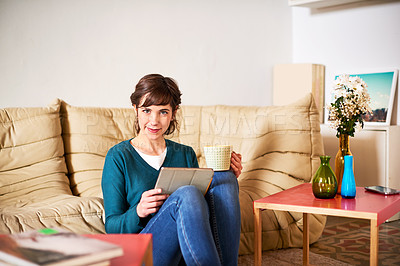 Buy stock photo Portrait of a young woman sitting on her living room floor using a digital tablet