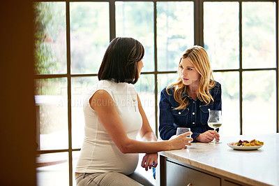 Buy stock photo Shot of two friends talking together while sitting at a dining table at home
