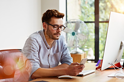 Buy stock photo Shot of a young man reading a text message while working on a computer in his home office