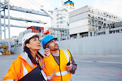 Buy stock photo Shot of two coworkers in protective workwear standing on a large commercial dock