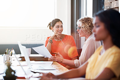 Buy stock photo Shot of two coworkers discussing paperwork at a desk in an office
