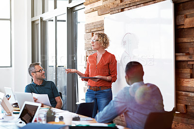 Buy stock photo Shot of a female office worker giving a financial presentation to her colleagues