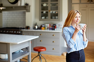 Buy stock photo Shot of a young woman drinking a coffee while looking through her kitchen window