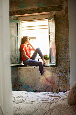 Buy stock photo Shot of an attractive young woman sitting on a window sill at home