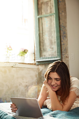 Buy stock photo Shot of a young woman lying on her bed using a digital tablet