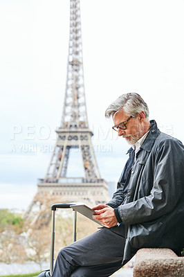 Buy stock photo Shot of a handsome mature man using a digital tablet in Paris with the Eiffel Tower in the background