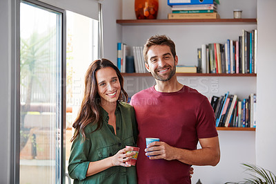 Buy stock photo Portrait of a smiling young couple standing together in their living room drinking coffee