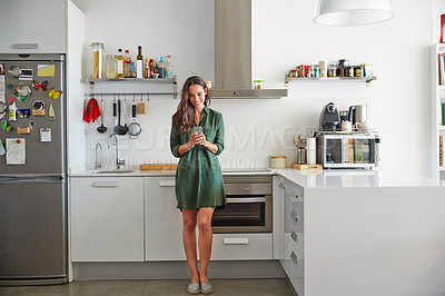 Buy stock photo Shot of a smiling young women standing in her kitchen in the morning sending a text message