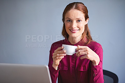 Buy stock photo Portrait of a young woman drinking a cup of coffee while working on a laptop at a desk in an office