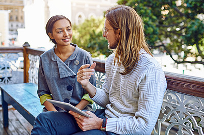 Buy stock photo Shot of two young designers sitting together on a bench outside of their office using a digital tablet