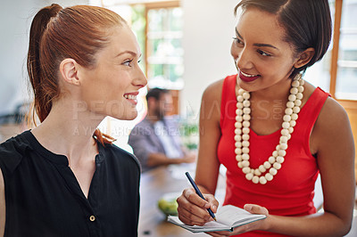 Buy stock photo Shot of two young colleagues talking together while working in an office