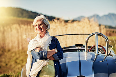 Buy stock photo Shot of a senior woman posing next to a convertible while out on a roadtrip