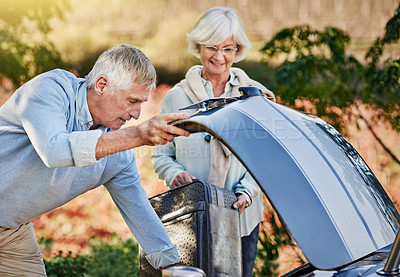 Buy stock photo Shot of a senior couple checking the engine of their convertible while out on a roadtrip
